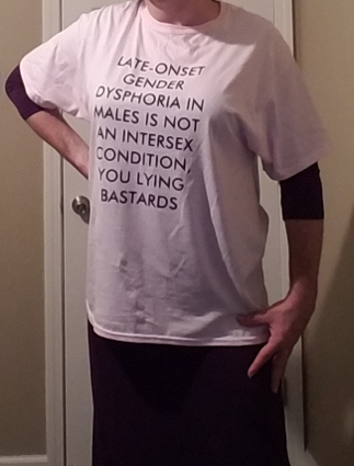 "torso shot of crossdressed male wearing ""LATE ONSET GENDER DYSPHORIA IN MALES IS NOT AN INTERSEX CONDITION"" T-shirt over purple dress"